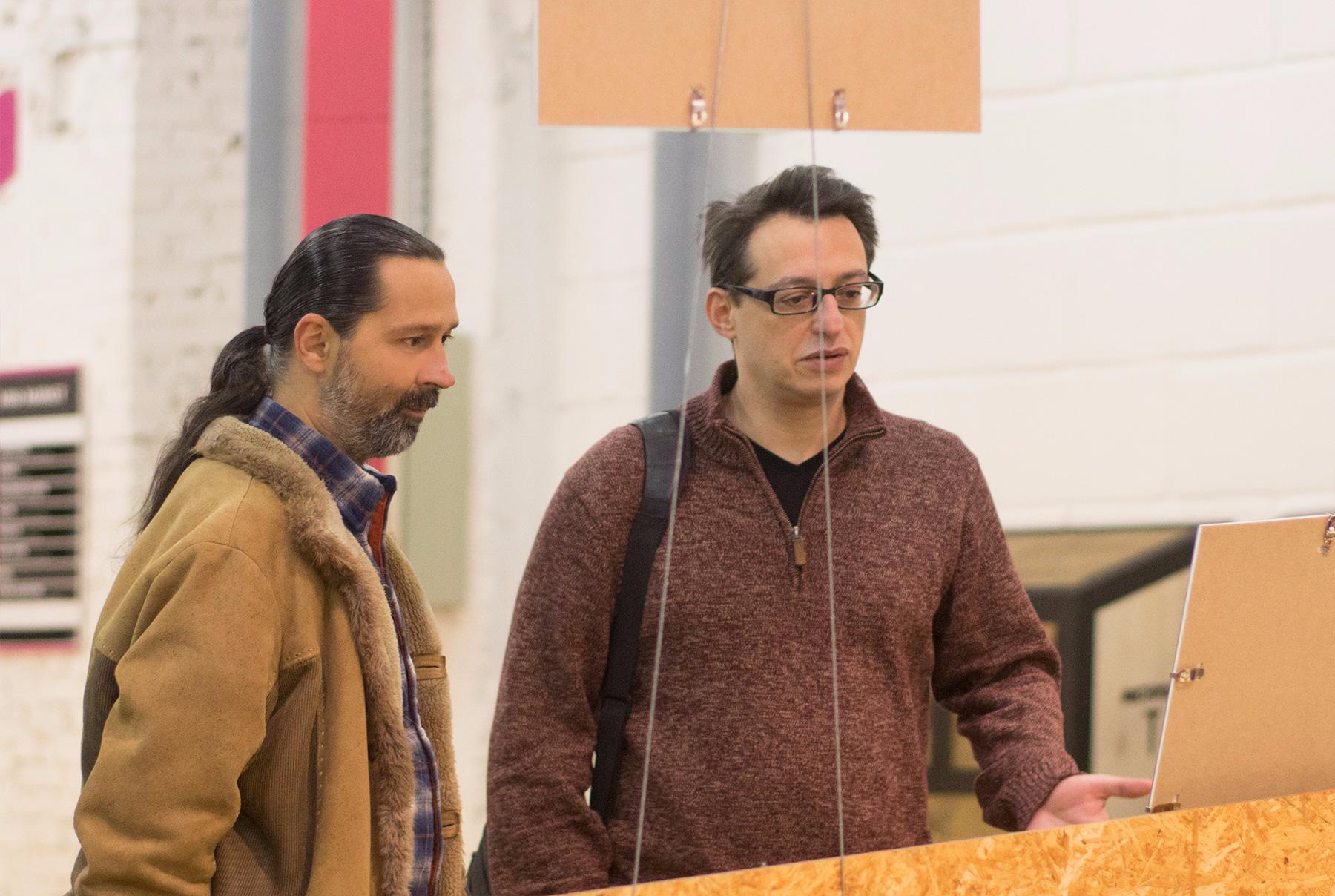 Алексей Звягинцев и Игорь Борщевский рассматривают выставку.